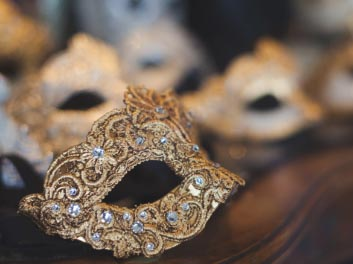 gold mask in focus with other masks in background