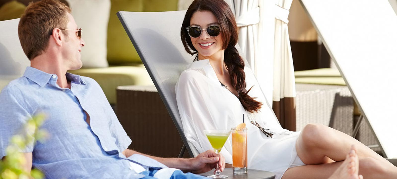 Happy young couple with drinks looking at each other while relaxing on lounge chairs