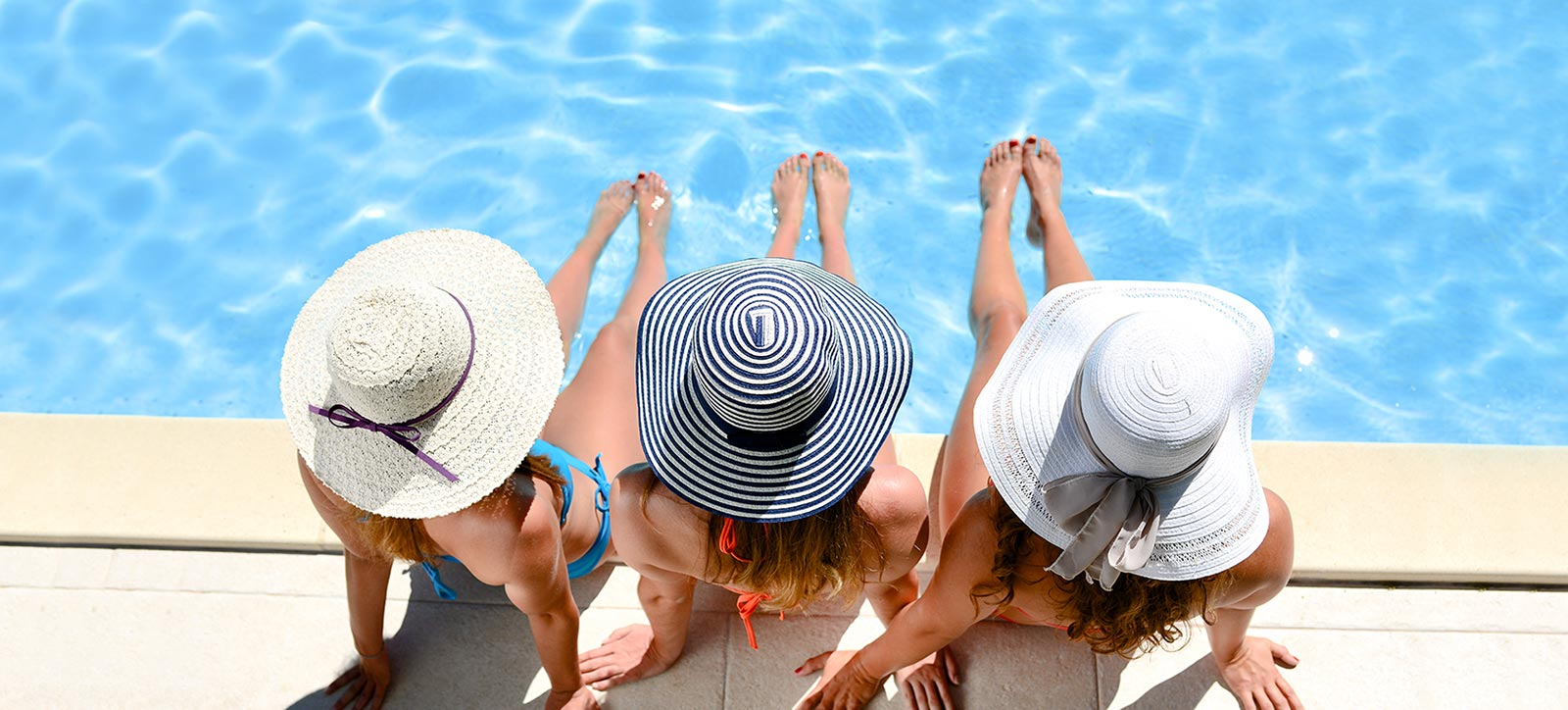 three women lounging in front of pool