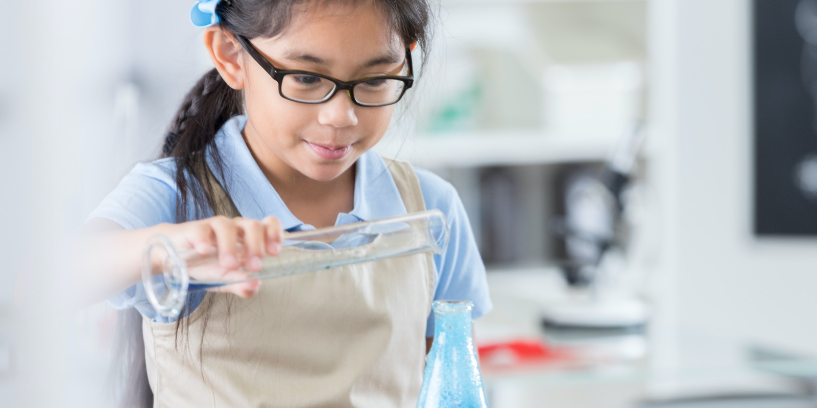 girl in chemistry class pouring into flask