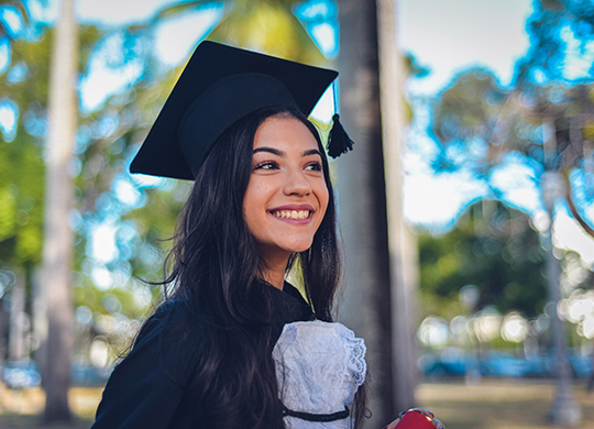 A young woman wearing a cap and gown