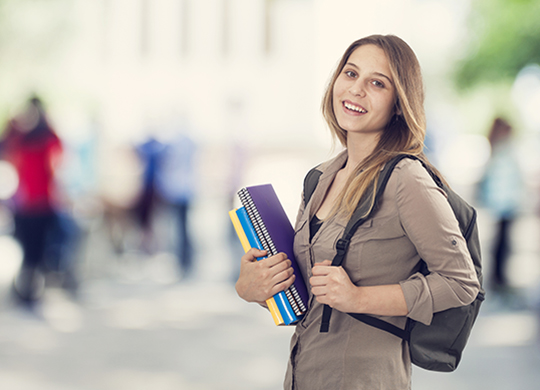 student holding books and backpack at school